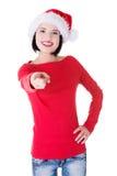 La mujer atractiva que lleva el sombrero de santa está señalando. Foto de archivo libre de regalías