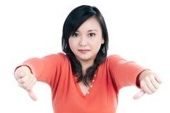 La mujer atractiva que muestra los pulgares abajo firma Foto de archivo