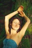La mujer atractiva que presenta en un árbol en la madera Fotos de archivo