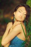 La mujer atractiva que presenta en un árbol en la madera Imágenes de archivo libres de regalías