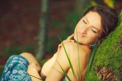 La mujer atractiva que presenta en un árbol en la madera Imagenes de archivo