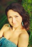 La mujer atractiva que presenta en un árbol en la madera Imagen de archivo libre de regalías