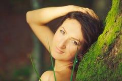 La mujer atractiva que presenta en un árbol en la madera Fotos de archivo libres de regalías