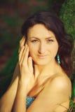 La mujer atractiva que presenta en un árbol en la madera Fotografía de archivo libre de regalías