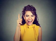 La mujer atractiva que señala el finger para arriba tiene una idea Imagen de archivo