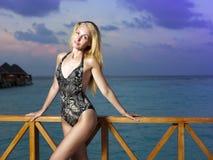 La mujer atractiva que se opone en un bañador al mar de la tarde maldives Imagenes de archivo
