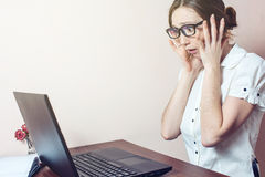 La mujer atractiva que trabaja en la oficina con el ordenador portátil ase su cabeza Foto de archivo