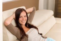 La mujer atractiva relaja el sofá del cuero de la sala de estar Foto de archivo