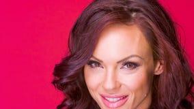 La mujer atractiva se lame los labios mientras que está aislada en rojo metrajes