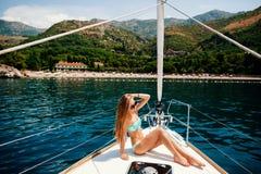 La mujer atractiva se relaja en el yate en el mar Fotografía de archivo libre de regalías
