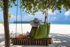 La mujer atractiva se relaja en una playa tropical imagen de archivo