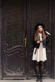 La mujer atractiva se vistió en la ropa de moda que sostenía el teléfono móvil mientras que se oponía a puerta retra con el espac Imágenes de archivo libres de regalías