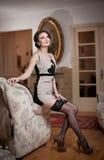 La mujer atractiva sonriente feliz que lleva un vestido elegante y las medias negras que se sientan en el sofá arman Muchacha sen Imagen de archivo libre de regalías