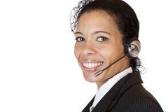 La mujer atractiva sonriente hace con el receptor de cabeza una llamada Imagen de archivo libre de regalías