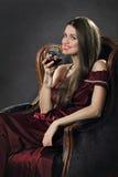 La mujer atractiva sonriente presenta con un vidrio de vino rojo Fotos de archivo libres de regalías