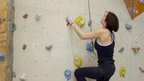 La mujer atractiva sube activamente en la pared que sube dentro metrajes