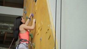 La mujer atractiva sube para arriba en rockwall en club de deportes almacen de metraje de vídeo