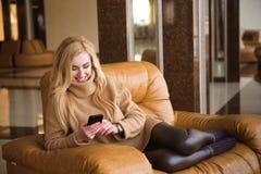 La mujer atractiva tiene un descanso para tomar café usando su teléfono móvil imagenes de archivo