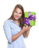 La mujer atractiva tiene un regalo con la cinta en su mano Fotografía de archivo