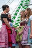 La mujer atractiva y alegre en el alemán Oktoberfest con el dirndl tradicional se viste, grande rueda adentro el fondo Imagenes de archivo
