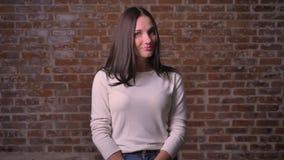 La mujer atractivamente está sonriendo, está cayendo su pelo en el otro lado y coqueting con una cámara almacen de video