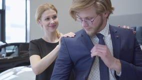 La mujer ayuda a su marido a llevar una situación de la chaqueta en la sala de exposición del coche Hombre de negocios y su espos almacen de video