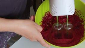 La mujer azota el puré de la clara de huevo y del arándano Con la ayuda de una licuadora Para la preparaci?n de la melcocha metrajes