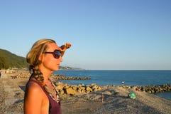 Mujer por el mar en luz del sol de la tarde imagen de archivo libre de regalías