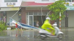 La mujer barre el agua de la entrada del edificio después de lluvia del huracán