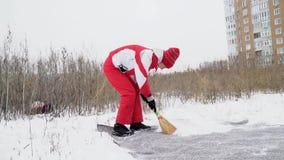 La mujer barre la nieve de la alfombra almacen de metraje de vídeo