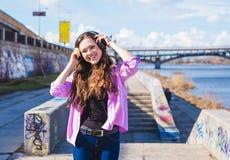 La mujer bastante adolescente de los jóvenes disfruta de música en parque de la ciudad cerca del río Imagen de archivo libre de regalías