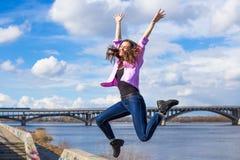 La mujer bastante adolescente de los jóvenes disfruta de música en parque de la ciudad cerca del río Imágenes de archivo libres de regalías
