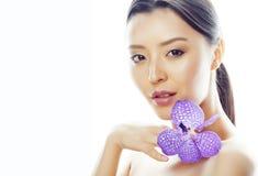 La mujer bastante asiática de los jóvenes con cierre púrpura de la orquídea de la flor para arriba aisló el balneario, concepto d fotos de archivo libres de regalías