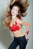 La mujer bastante atractiva con el pelo largo en rojo bordó el mono Fotos de archivo libres de regalías
