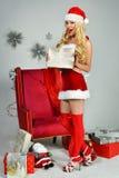 La mujer bastante atractiva con las piernas largas que llevan a Santa Claus viste Fotografía de archivo