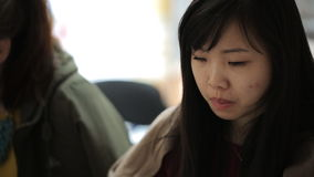 La mujer bastante china se sienta en la tabla en oficina con sus colegas almacen de metraje de vídeo