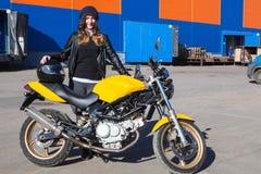 La mujer bastante feliz con su moto entregada se coloca al lado del almacén de la compañía de la carga, recibiendo la bici fotografía de archivo