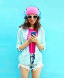 La mujer bastante fresca escucha la música en auriculares usando smartphone Foto de archivo libre de regalías