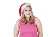 La mujer bastante gorda lleva el sombrero de la Navidad Imagenes de archivo
