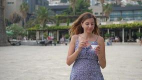 La mujer bastante joven camina abajo de la calle y come con un helado de la cuchara almacen de metraje de vídeo