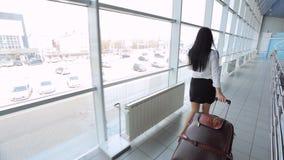 La mujer bastante joven camina a través de aeropuerto con equipaje almacen de video