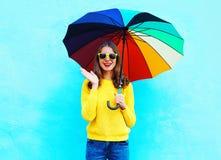 La mujer bastante joven chocada con el paraguas colorido en día del otoño sobre el fondo azul que llevaba un amarillo hizo punto  Fotos de archivo libres de regalías
