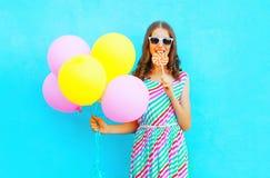 La mujer bastante joven con los balones de un aire muerde un caramelo de la piruleta Imagen de archivo