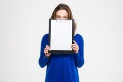 La mujer bastante joven cubrió su cara con el tablero en blanco Fotografía de archivo