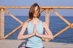 la mujer bastante joven del ajuste que hace yoga ejercita en la playa del verano Imagen de archivo libre de regalías