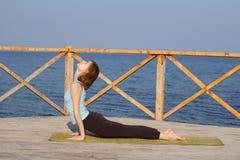la mujer bastante joven del ajuste que hace yoga ejercita en la playa del verano Foto de archivo libre de regalías