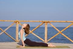 la mujer bastante joven del ajuste que hace yoga ejercita en la playa del verano Fotos de archivo