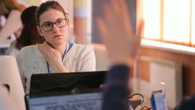 La mujer bastante joven en gesticular de los vidrios explica algo a otra hembra metrajes