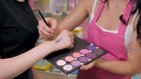 La mujer bastante joven en tienda de la perfumería elige los cosméticos con cosultant almacen de metraje de vídeo