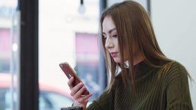 La mujer bastante joven en un suéter elegante se sienta en el café, bebe el café, manda un SMS a los mensajes y sonríe feliz almacen de video